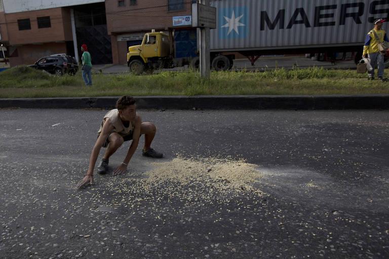 Adolescente se apressa para recolher milho que caiu de caminhão saqueado em Puerto Cabello