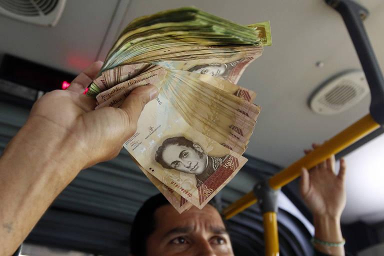 O venezuelano Jorge Gutierrez segura bolívares que busca trocar por pesos colombianos em Bogotá
