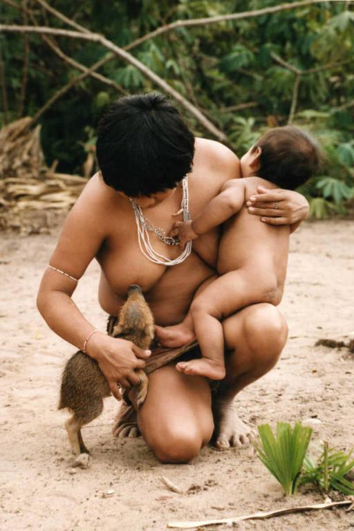 Com o filho Tamataí no colo, a índia Huyra, da tribo dos guajás, amamenta filhote de porco-do-mato