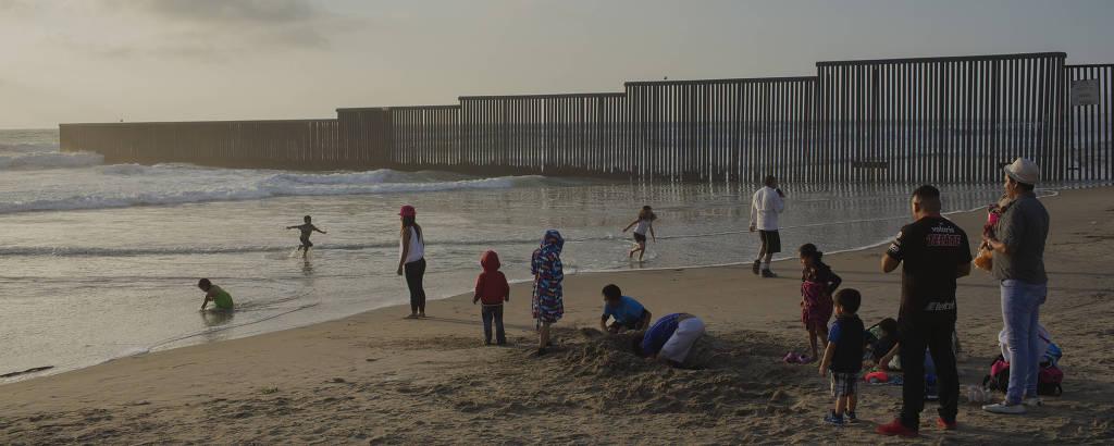 Pessoas na praia de Tijuana, no México, cortada pelo muro que marca a fronteira com a cidade de San Diego, nos Estados Unidos