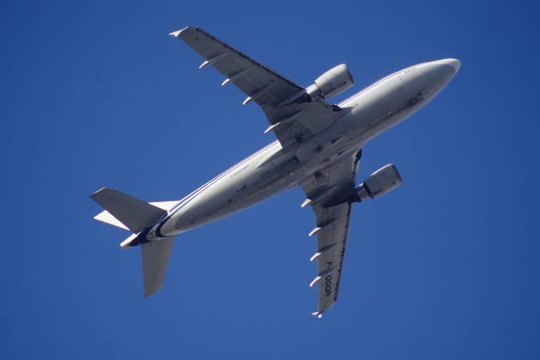 Avião em subida contra céu azul
