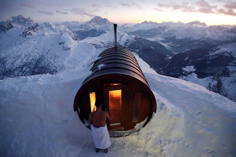 Pessoa entra em sauna com formato de barril no topo monte coberto por neve. Na paisagens, várias montanhas nevadas.