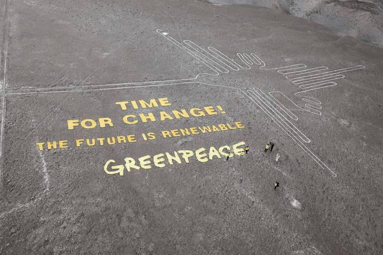 """Próximo ao colibri desenhado nas linhas de Nazca, pessoas do Greenpeace fazem protesto. Os manifestantes estenderam faixas que formam as frases: """"É tempo de mudança! O futuro é renovável""""."""