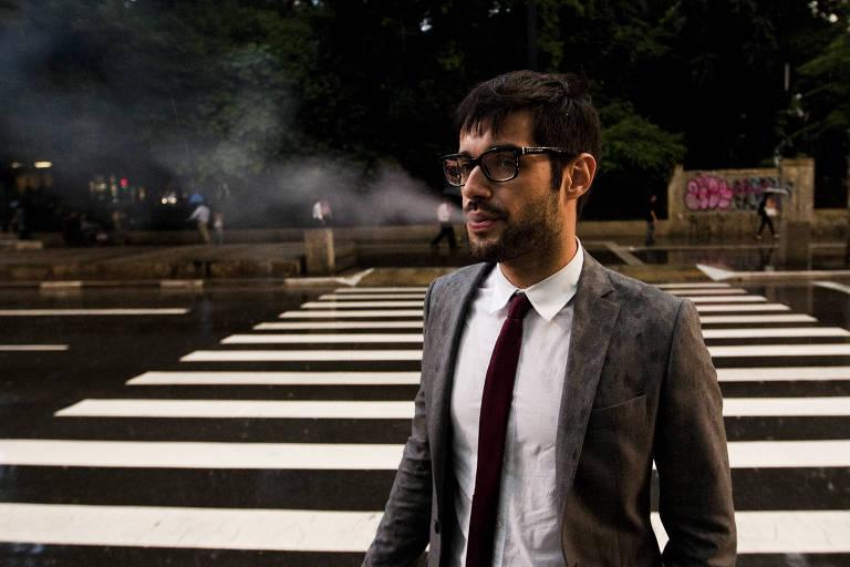 Homem fumando atravessa faixa de pedestres na avenida Paulista