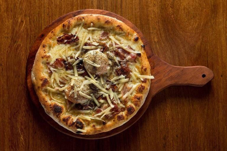 Pizza Carbonara, com três tipos de queijo, bacon e ovos, servida na Pinocchio Cucina