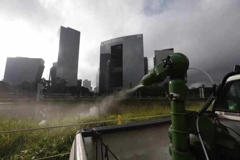 Força-tarefa especial de combate a pernilongos na região do rio Pinheiros, em janeiro de 2017; na foto, um pulverizador apoiado na caçamba de um veículo lança produto químico nas margens do rio Pinheiros, em São Paulo; ao fundo grandes edifícios