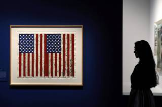 EMBARGOED UNTIL 07/03/17 0001 GMT An employee poses next to a print of Jasper Johns' 'Flags I' at the exhibition