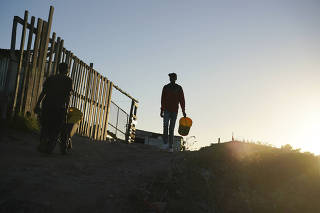 Residents collect water from a communal tap in an informal settlement in Mitchells Plain outside of Cape Town, South Africa.