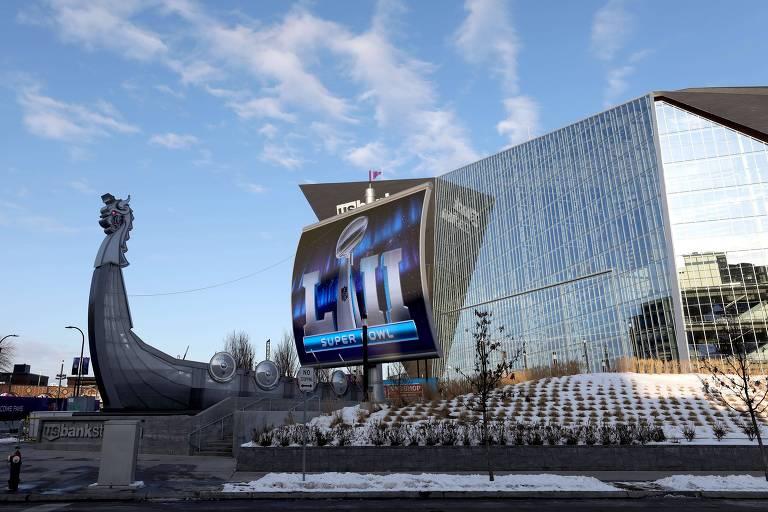 Vista da arena US Bank Stadium, que se assemelha a um barco viking. O estádio possui a fachada repleta de vidros. À frente, um telão indica que o Super Bowl será realizado no local.