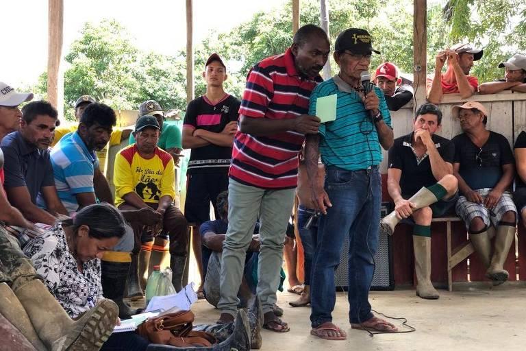 Cacique Osvaldo Wauru fala para índios enquanto homem tenta passar dar para ele uma lista com garimpeiros que prometeram dar ouro para o poço