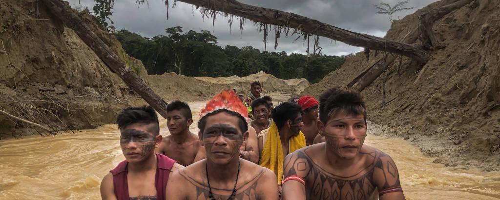 Guerreiros mundurucus cruzam de barco garimpo de ouro que devastou o rio das Tropas e parte do seu território, no município de Jacareacanga, sudoeste do Pará.