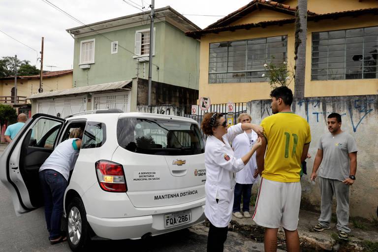 Homem com camisa amarela em pé e de costas, parado ao lado da calçada, enquanto recebe vacina por enfermeira vestida com jaleco ao seu lado