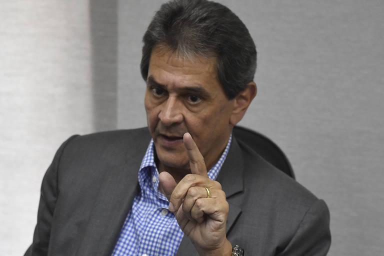 O presidente nacional do PTB, Roberto Jefferson, está sentado em uma cadeira (ele aparece na foto do peito para cima) e gesticula com o dedo indicador da mão esquerda. Ele usa camisa e paletó, sem gravata. O fundo é uma parede branca