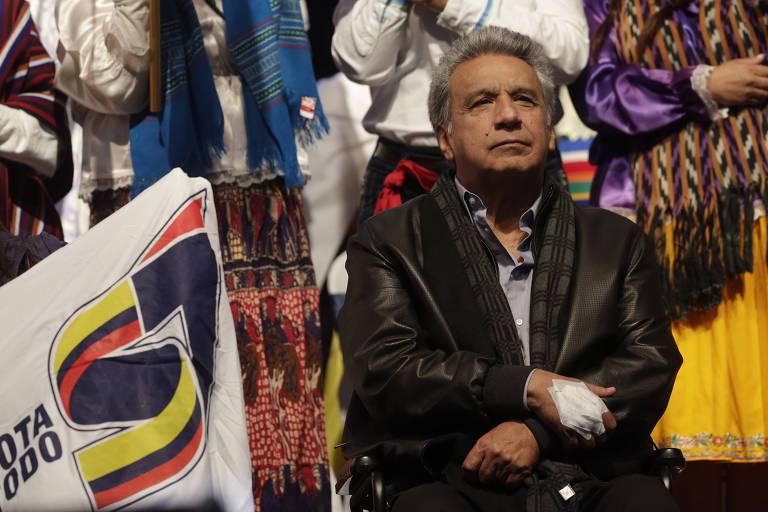 De jaqueta de couro e sentado em sua cadeira de rodas, o presidente do Equador, Lenín MorenoIn, observa a plateia em comício antes de referendo constitucional no paí; atrás dele há populares em trajes típicos indígenas e uma bandeira