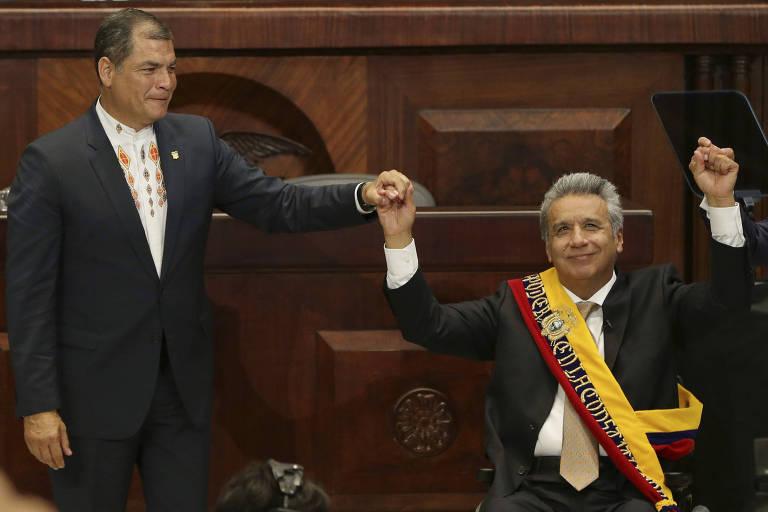 O presidente do Equador, rafael Correa, à esquerda, segura a mão direita de seu sucessor e então afilhado político, Lenín Moreno, que veste a faixa presidencial amarela, azul e vermelha e ergue os braços em celebração sentado em sua cadeira de rodas no Congresso equatoriano