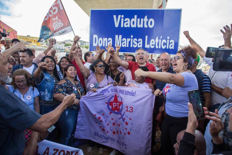 """Militantes do PT vestidos de lilás e vermelho e de braços levantados diante da placa azul """"viaduto Dona Marisa Letícia"""""""