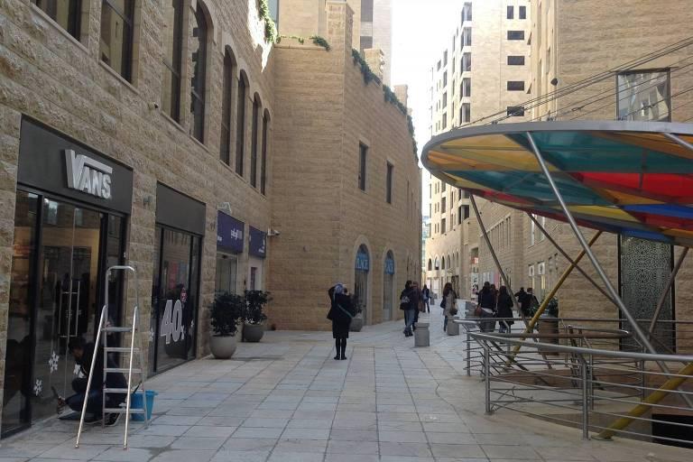 O centro comercial da cidade palestina de Rawabi, com poucos passantes, onde se vê lojas à esquerda e um toldo multicolorido à direita