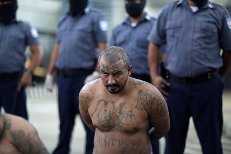 Um homem quase completamente tatuado com símbolos de gangue e careca se ajoelha de costas para policiais em um páteo de prisão em El Salvador