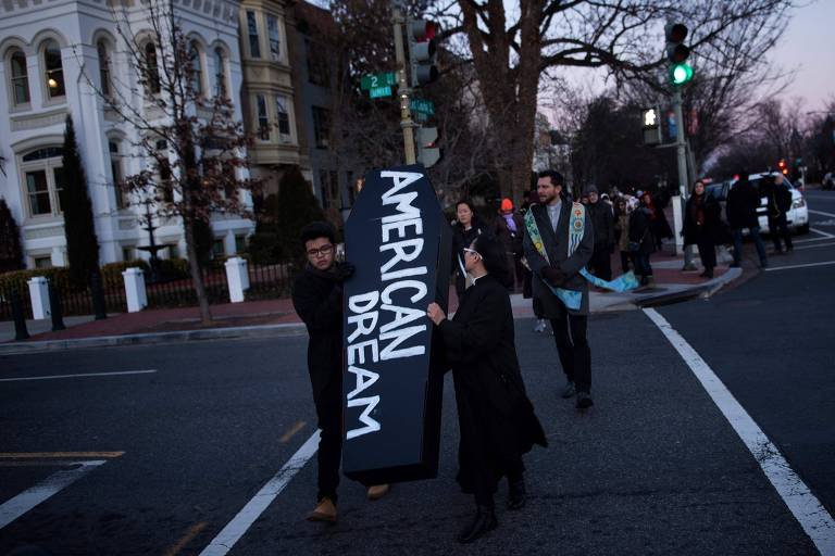 """Ativistas carregam por Washington faixa de protesto com os dizeres """"sonho americano"""" antes do Discurso sobre o Estado da União, proferido por Trump"""