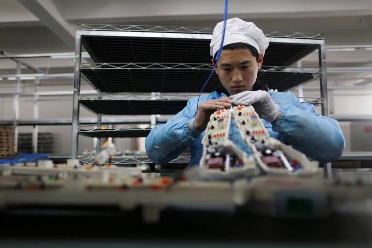 Trabalhador em fábrica de eletrônicos da China; compra em massa da Huawei contribui para desabastecimento global