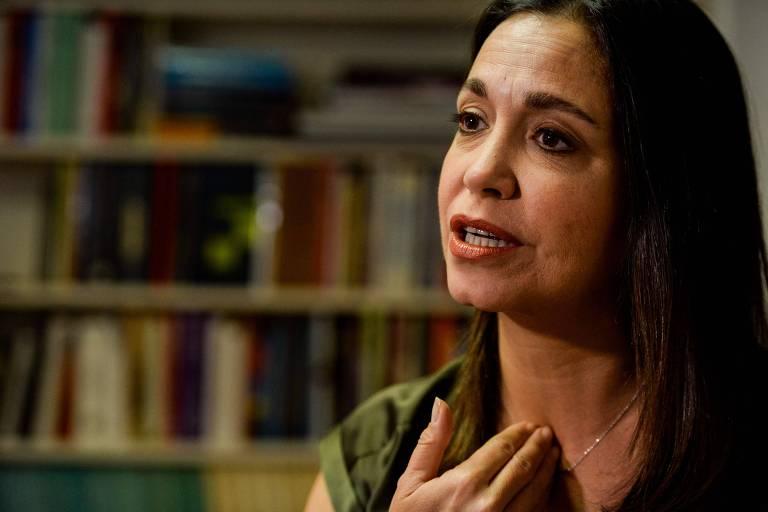 Com a mão no pescoço, María Corina Machado conversa com jornalistas no escritório de sua casa; ao fundo, sua estante de livros