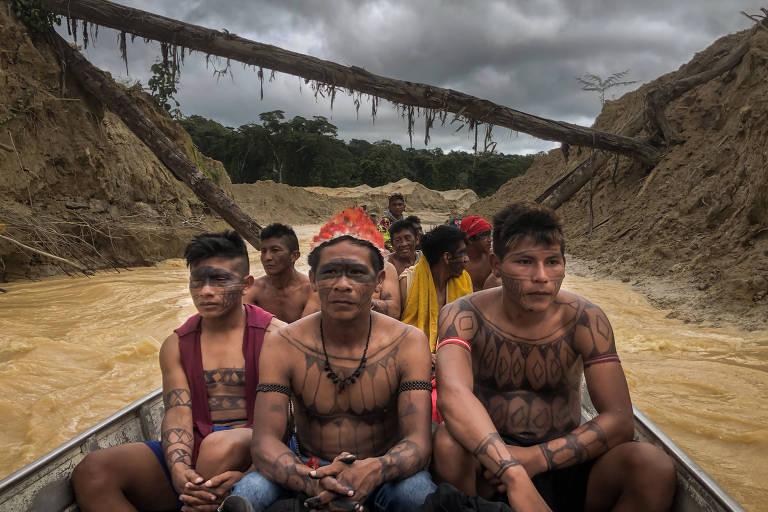 Guerreiros mundurucus navegam numa canoa pelo lamacento Rio das Tropas, no garimpo de ouro que devastou parte do  seu território, no município de Jacareacanga, sudoeste do Pará.