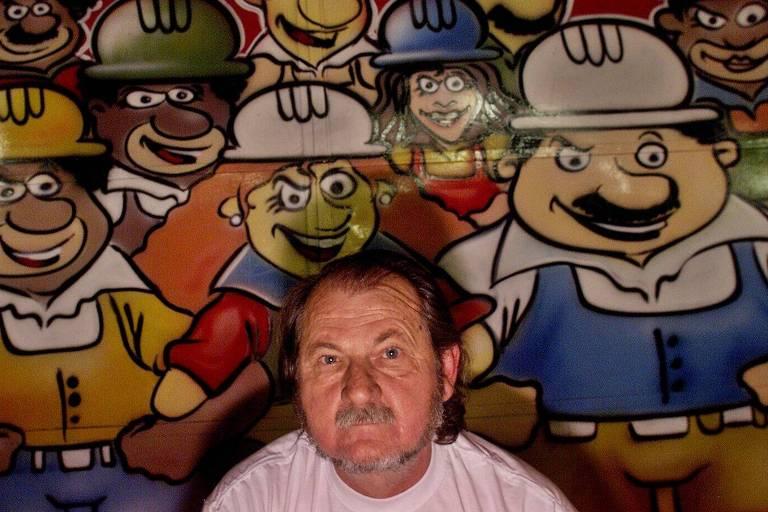 Stanislaw Szermeta, então com 58 anos, militante do PSOL, em frente a um painel colorido com desenhos de operários.