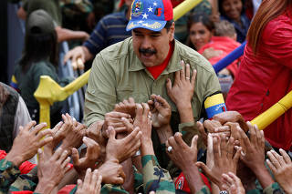 Venezuela's President Nicolas Maduro greets supporters as he arrives for a rally to commemorate the 26th anniversary of late Venezuelan President Hugo Chavez failed coup attempt in Caracas