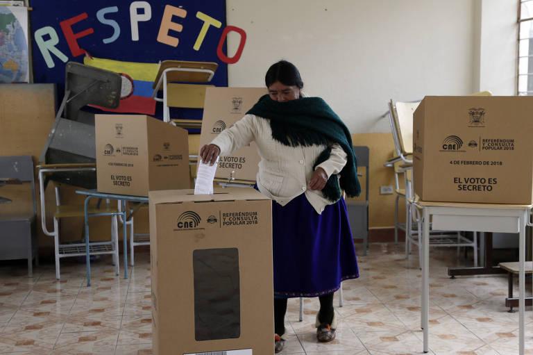 Mulher deposita voto na urna em seção eleitoral de Quito durante referendo neste domingo (4) no Equador