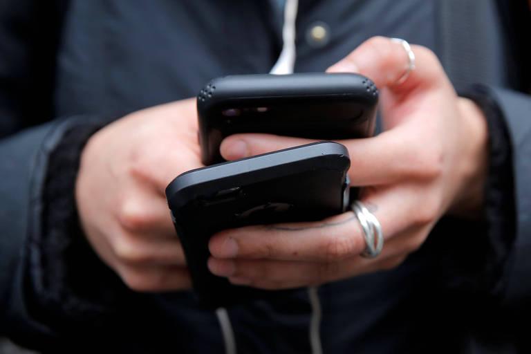 Mulher segura dois celulares enquanto acessa a internet