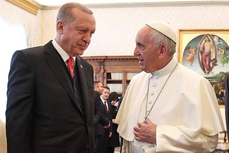 Homem de terno preto e gravata vermelha, à esquerda, papa à direita