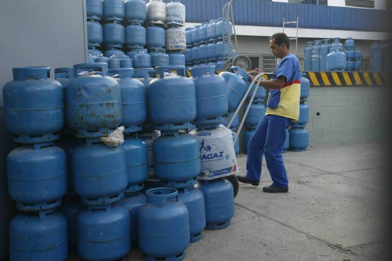 Homem carrega botijões de gás