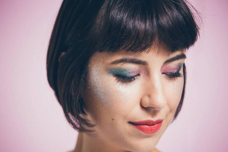 Mulher de cabelo curto usa brilho colorido nos olhos e nas têmporas