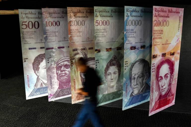 Banners replicando notas de bolívar são penduradas na porta do Banco Central da Venezuela; em leilão oficial moeda caiu 86% em relação ao euro