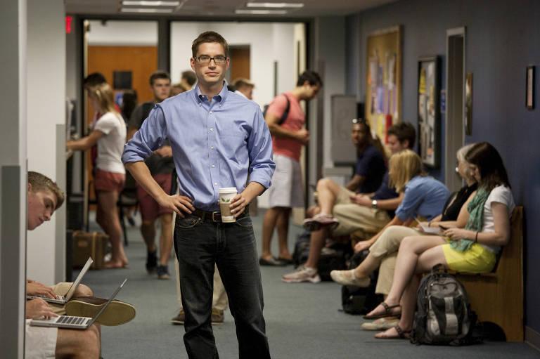 Cal Newport em pé no correto da universidade segurando um copo de café; ao fundo há alunos sentados no corredor