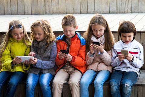 Outdoor portrait of cheerful girls and boys playing with phones, criancas , celular , tecnologia , virtual , infancia .  Credit: JackF/Fotolia ***DIREITOS RESERVADOS. NÃO PUBLICAR SEM AUTORIZAÇÃO DO DETENTOR DOS DIREITOS AUTORAIS E DE IMAGEM***