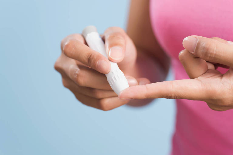 Mulher pica o dedo para medir a glicose no sangue