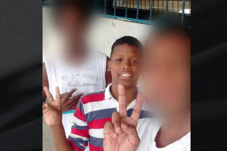 Adolescente Jeremias de camisa listrada de vermelho e azul faz gestos de paz e amor ao lado de dois colegas