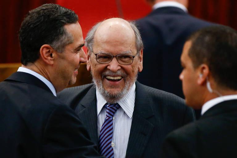 Advogados de terno escuro conversam e sorriem na posse de Luiz Fux no TSE