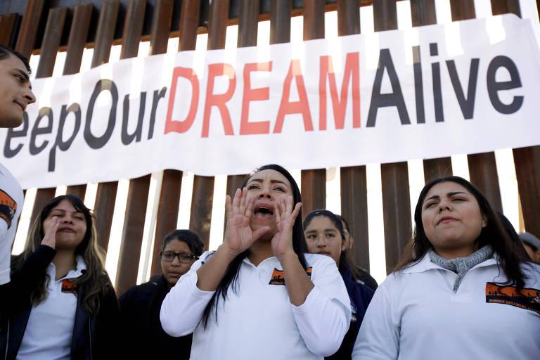 Jovens imigrantes pedem manutenção das regras para os dreamers em protesto na cerca da fronteira entre San Diego  e Tijuana, no México