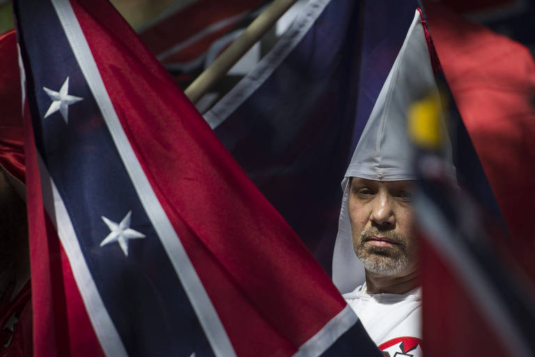 Homem com capuz da Ku Klux Klan passa entre bandeiras confederadas durante manifestação supremacista em Charlottesville, nos EUA, em julho