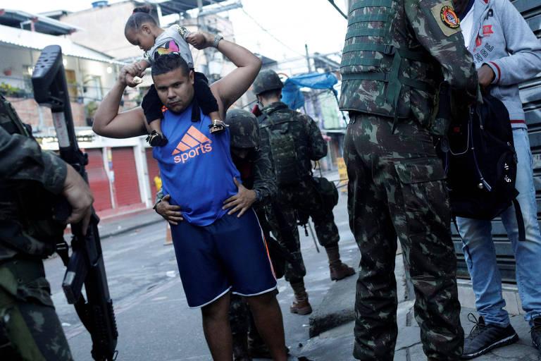 Membros das Forças Armadas revistam moradores da Cidade de Deus durante operação policial no Rio