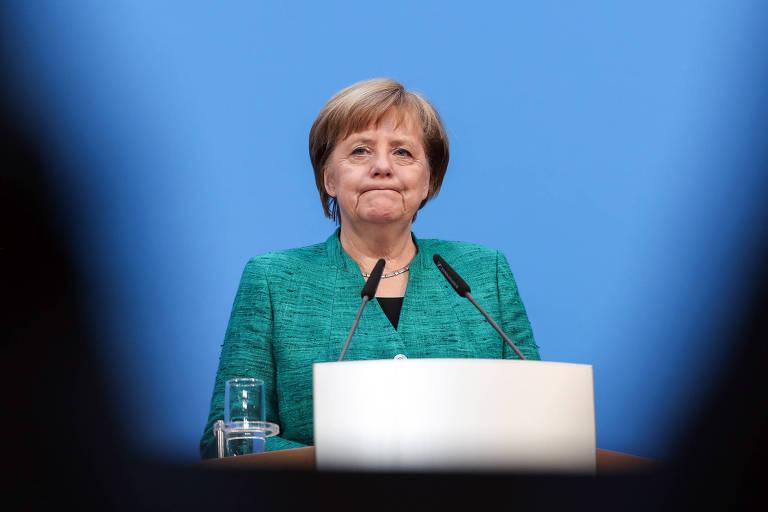 A chanceler alemã, Angela Merkel, de terno verne fala ao microfone