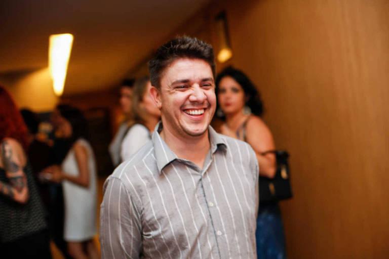 O humorista Oscar Filho está no centro da foto, mostrado da cintura para cima. Ele tem cabelos curtos, castanhos e lisos, com uma pequena franja. Ele está ligeiramente virado para a direita, a partir da visão do observador, e sorri com os olhos um pouco fechados. Usa uma camisa social de mangas compridas cinza com finas listras brancas