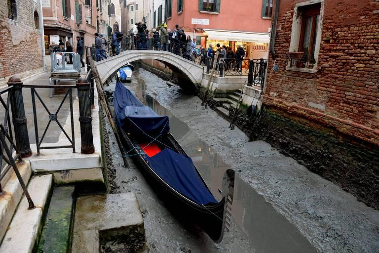 A foto mostra uma gôndola parada no barro de um dos canais de Veneza que, neste caso, é bastante estreito. Ao fundo da imagem, uma pequena ponte que cruza o canal e tem o formato de um semi-círculo, há diversos turistas fotografando o cenário