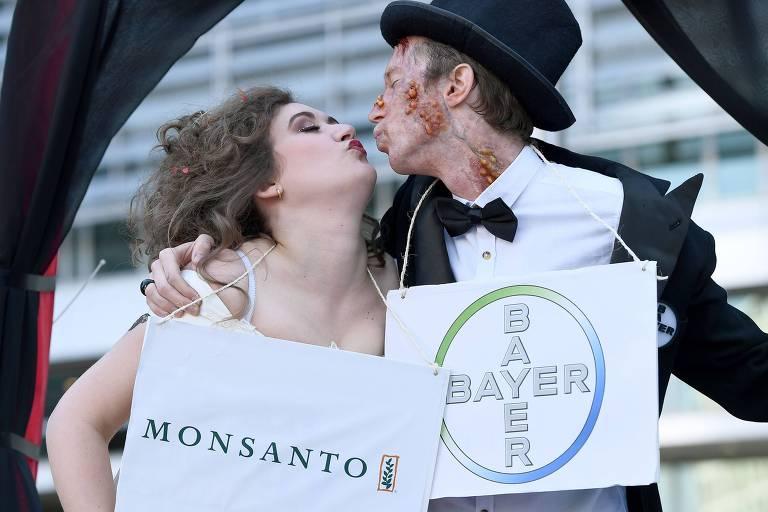 Ativistas vestidos de noiva e noivo seguram placas da Bayer e da Monsanto em protesto contra a fusão