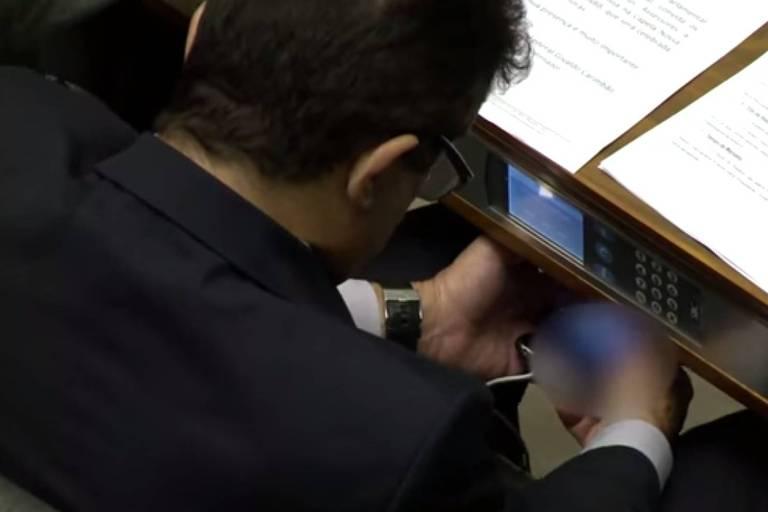 Homem com a cabeça abaixada vendo vídeo por baixo da mesa