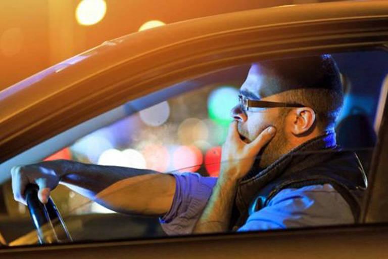 Homem boceja enquanto conduz carro