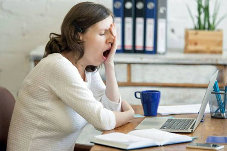 Mulher boceja sentada em frente a um notebook