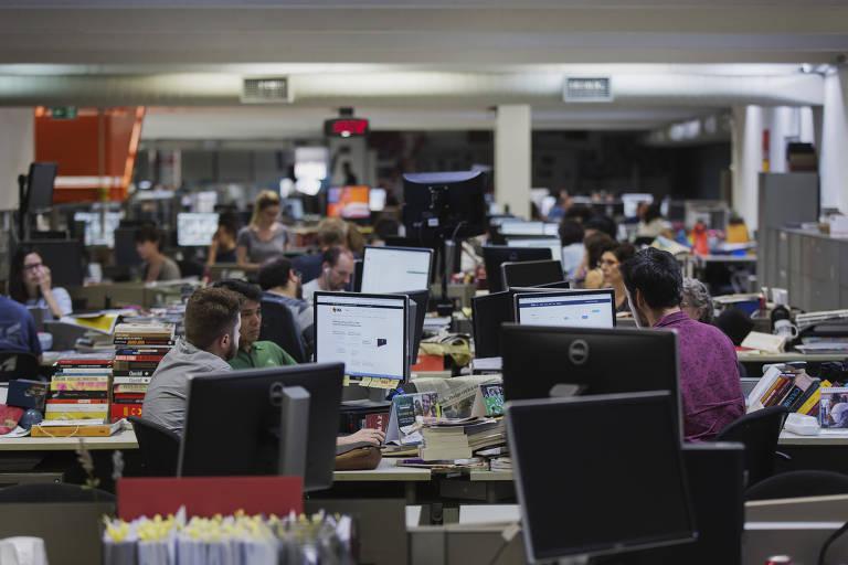 Jornalistas trabalham em computadores em várias mesas